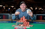 Jeffrey Tebben shows off his Event 24 Championship Bracelet, chips, and winning hand