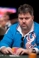 Sergey Altbregin watches the action at his table while clinching his cards.