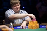 Peter Gelencser reaches for chips at the final table of Event #7.