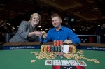 Joshua Tieman and Nikki Ivey hold up his 2010 WSOP championship bracelets.
