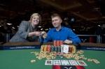 Joshua Tieman and Nikki Ivey hold up his 2010 WSOP championship bracelets.