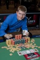 Joshua Tieman leans over his winning chip stack.