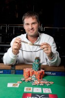 John Barch winner of Event 20 holds his new bracelet while his card protector holds some chips.